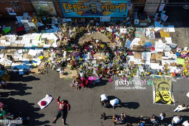 TOPSHOT An aerial view shows people gathering to pay tribute at a makeshift memorial in honour of George Floyd on June 3 2020 in Minneapolis...