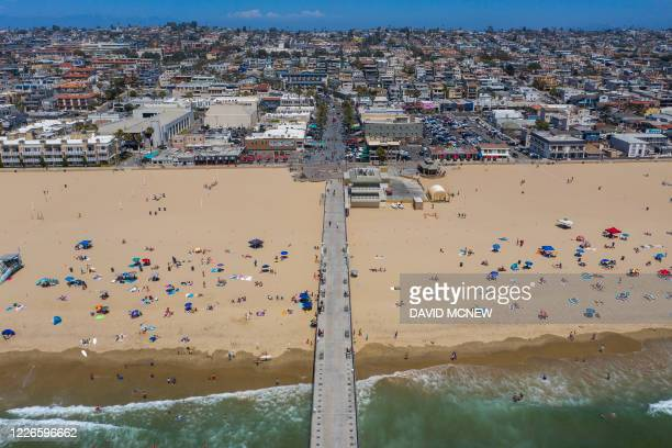 An aerial view shows people on the beach during a heatwave as coronavirus cases reach new record levels in states across the nation, in Hermosa...