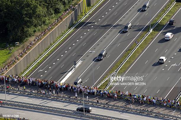 An aerial view shows people standing on a bridge looking at a convoy of hearses carry the remains of the victims of the Malaysia Airlines flight MH17...