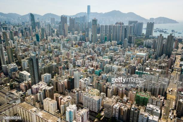 An aerial view shows residential and commercial buildings in the Kowloon district and ships sailing in Hong Kong's Victoria Harbour on October 30 2018