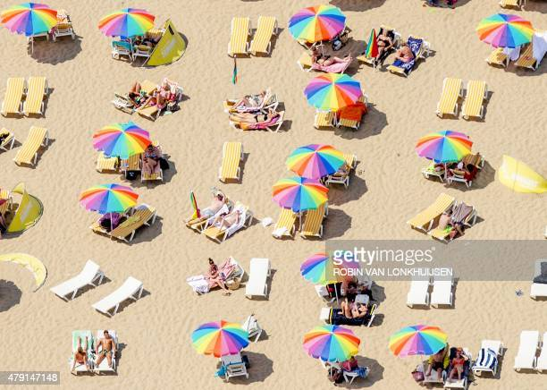 An aerial view shows sunbathers sitting under colorful umbrellas on the beach in Scheveningen the Netherlands on July 1 on a warm summer day A...