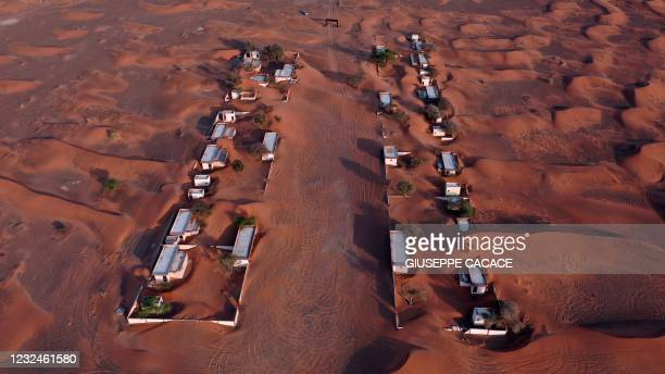 An aerial view shows the abandoned village of Al-Madam, bordering the Gulf Emirate of Sharjah, half buried in the desert sand, on April 22, 2021.