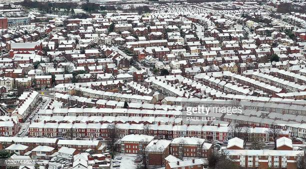 An aerial view shows the snow-covered rooftops of houses in Birkenhead, north west England on January 23 as a Met office yellow weather warning for...