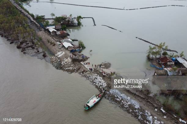 An aerial view shows volunteers and residents working to repair a damaged dam following the landfall of cyclone Amphan in Burigoalini on May 21 2020...