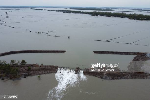 An aerial view shows water from a flooded crab farming area breaking through a damaged dam following the landfall of cyclone Amphan in Burigoalini on...