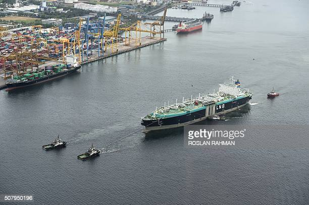 An aerial view taken from a helicopter shows a guided LNG tanker being towed along the Johor straits bordering Singapore on February 2 2016 AFP PHOTO...