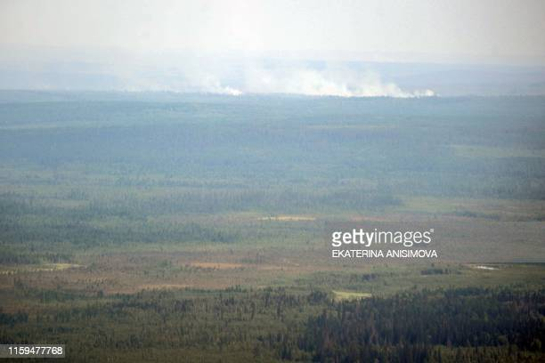 An aerial view taken from onboard a helicopter shows smoke from forest fires rising above the Boguchansky district of Russia's Krasnoyarsk Krai on...