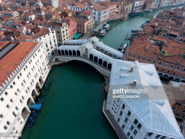 An aerial view taken on April 25, 2020 in Venice shows the Rialto bridge over the Grand Canal, during the country's lockdown aimed at curbing the...