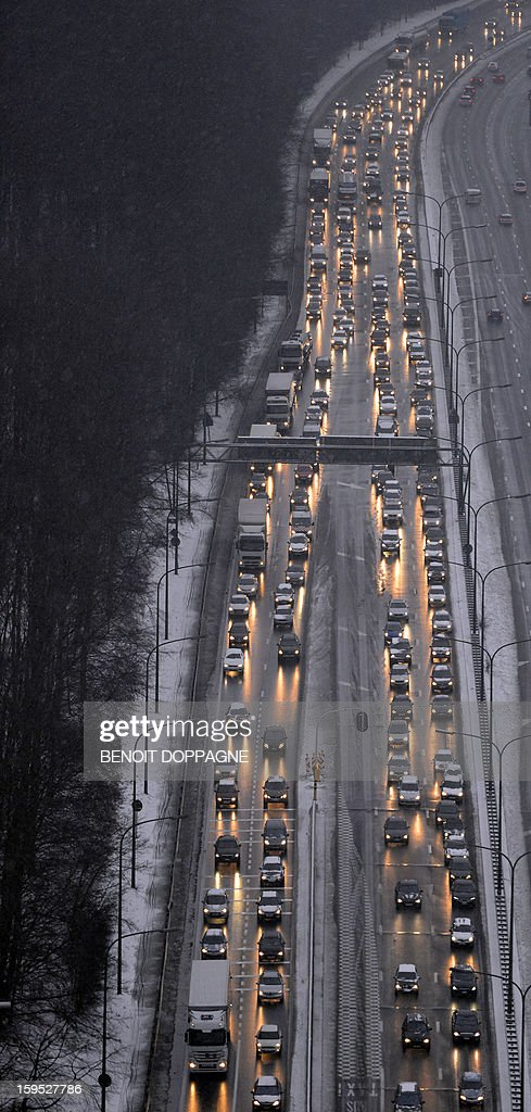 An aerial view taken on January 15, 2013 shows the morning traffic at the crossroads between E411 and Brussels' ring, as snow covers the country. Weather services predicted a lot of snowfall overnight. AFP PHOTO / BELGA - BENOIT DOPPAGNE'