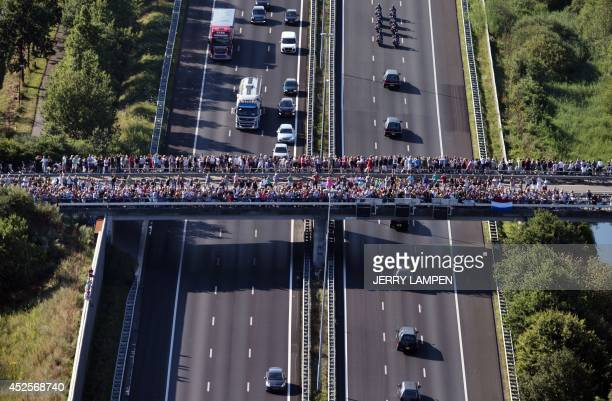 An aerial view taken on July 23 2014 shows people looking over a bridge the convoy of hearses carrying the bodies of victims of the downed Malaysia...