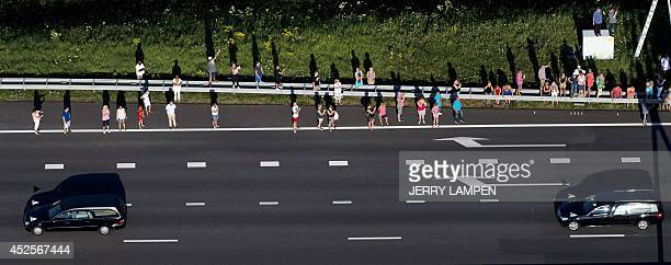 An aerial view taken on July 23 2014 shows people standing on the side of the road as the convoy of hearses carrying the bodies of victims of the...