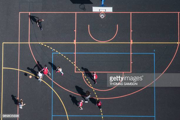 An aerial view taken on June 15 shows children playing basketball on a court west of Paris