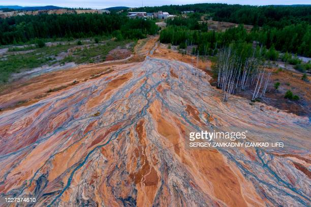 An aerial view taken on June 27, 2020 shows orange-coloured rivers fanning out over the forested landscape near a disused copper-sulphide mine near...