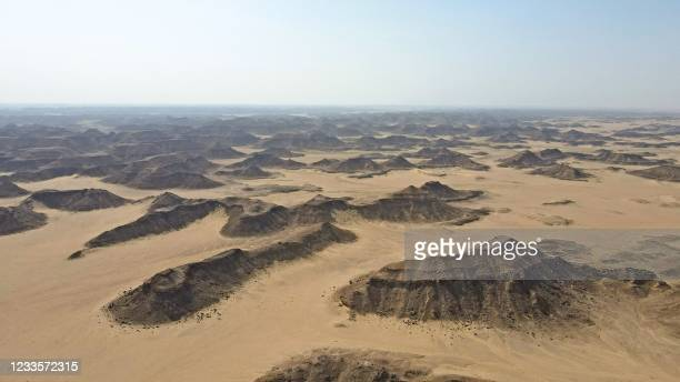 """An aerial view taken on June 6, 2021 shows the desert of Yemen's Al-Mahra province where the Well of Barhout known as the """"Well of Hell"""" is located...."""