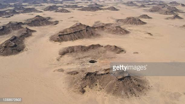 """An aerial view taken on June 6, 2021 shows the Well of Barhout known as the """"Well of Hell"""" in the desert of Yemen's Al-Mahra province. - Closer to..."""