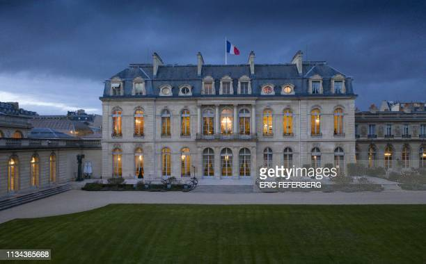 An aerial view taken on March 13, 2019 in Paris shows the Elysee Palace from the garden side with the French President's office at nightfall.