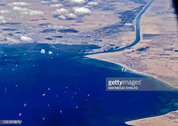 An aerial view taken on March 27, 2021 from the porthole of a commercial plane shows stranded ships waiting in queue in the Gulf of Suez to cross the...