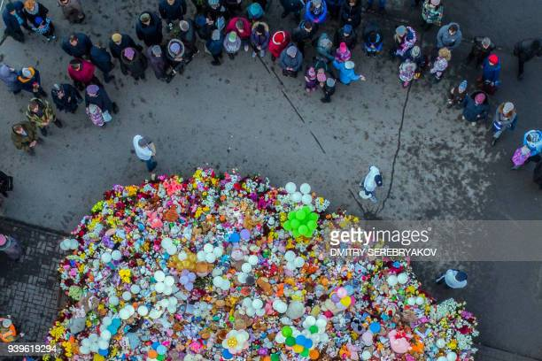 An aerial view taken with a drone on March 29 2018 shows people visiting a makeshift memorial in tribute to the victims of a shopping mall fire in...
