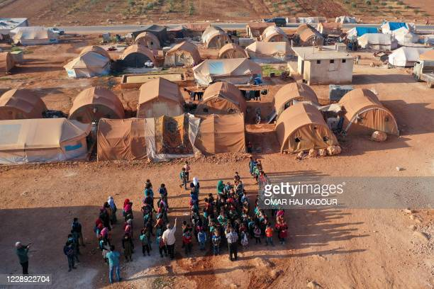 An aerial view taken on October 6 shows displaced Syrian youths standing in a queue ahead of classes, after tents were transformed to classrooms, at...