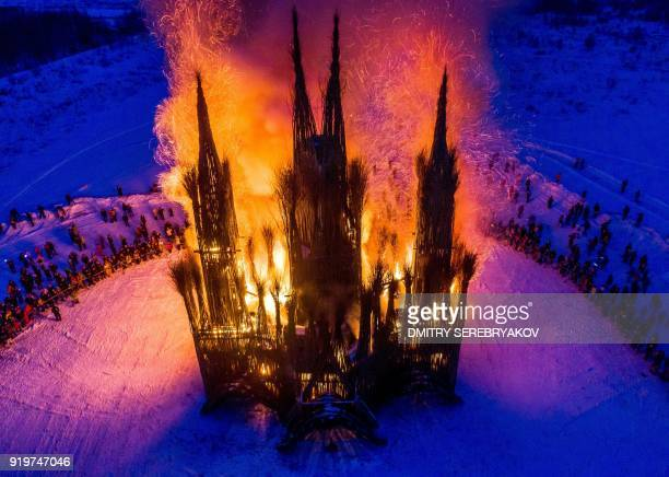 TOPSHOT An aerial view taken with a drone on February 17 2018 shows spectators as they watch the burning of a thirtymeter structure built of twigs...