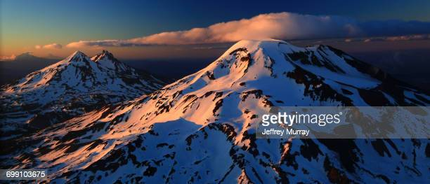 an aeriel view of the three sisters with mount jefferson and mount hood in the distance. - cascade range stock pictures, royalty-free photos & images
