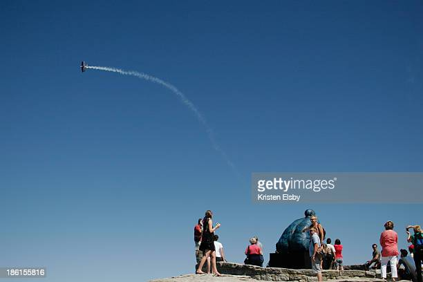 An aerobatic plane flies over the Bondi to Bronte cliff tops as visitors pose in front of artworks in the 2007 Sculpture by the Sea exhibition.