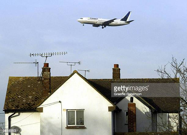 An aeroplane flies over houses during its approach to Stanstead Airport December 16 2003 in London The government is expected to announce plans for a...