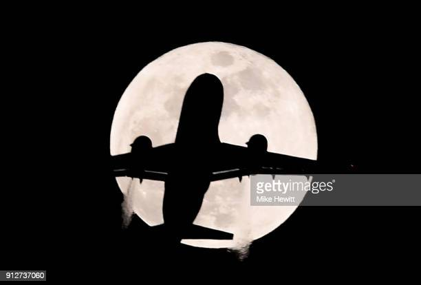 An aeroplane flies past the supermoon during the Premier League match between Chelsea and AFC Bournemouth at Stamford Bridge on January 31 2018 in...