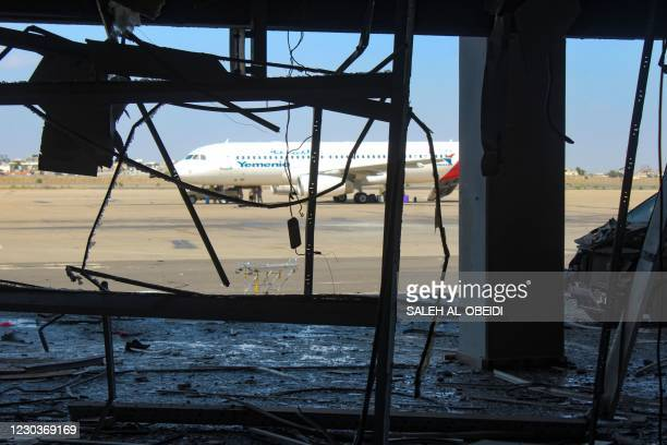 An aeroplane is pictured from inside the damaged airport of Yemen's southern city of Aden on December 31 a day after explosions rocked the building,...