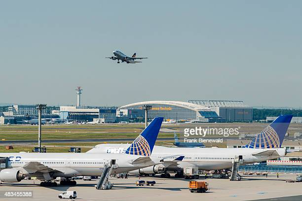 An aeroplane of the airline Lufthansa is taking off at Frankfurt International Airport two more aeroplanes are parking on the ground for maintainance