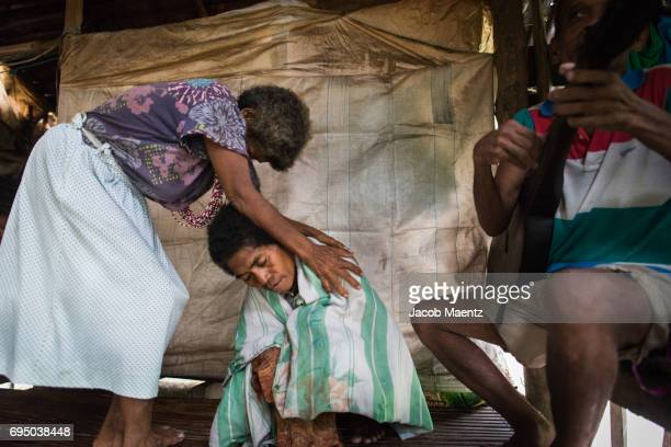 An Aeta anito (healer or medicine woman) performs a ritual to heal a member of her community.