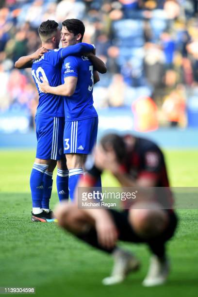 An AFC Bournemouth player looks dejected as James Maddison and Ben Chilwell of Leicester City celebrate following the Premier League match between...