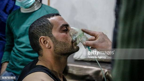 An affected man receives treatment after an alleged gas attack on Sakba and Hammuriye areas in Eastern Ghouta Syria on March 7 2018 According to...