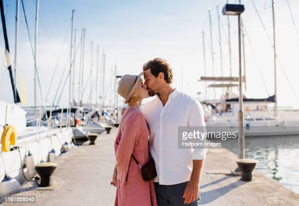 an affectionate couple standing outdoors on dock, kissing. - marina stock pictures, royalty-free photos & images