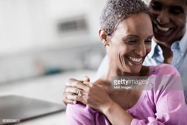 An affectionate mature African American couple, with their arms around each other in their home.