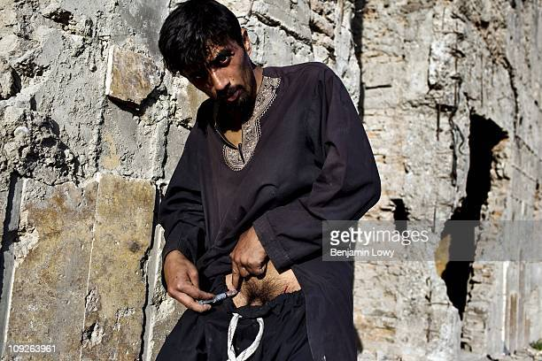 An Afghan addict shoots heroin into his groin in order to hide track marks from his family members on April 29 2009 in Kabul Afghanistan