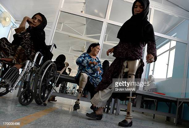 An Afghan amputee practices walking with her prosthetic leg at one of the International Committee of the Red Cross hospitals for war victims and the...