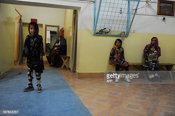 An Afghan amputee practices walking with her prosthetic legs at an International Committee of the Red Cross hospital for war victims and the disabled...