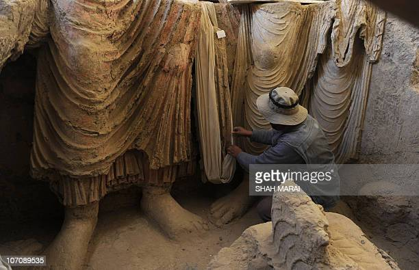 An Afghan archaeologist looks at the remains of Buddha statues discovered inside an ancient monastery in Mes Aynak in the eastern province of Logar...