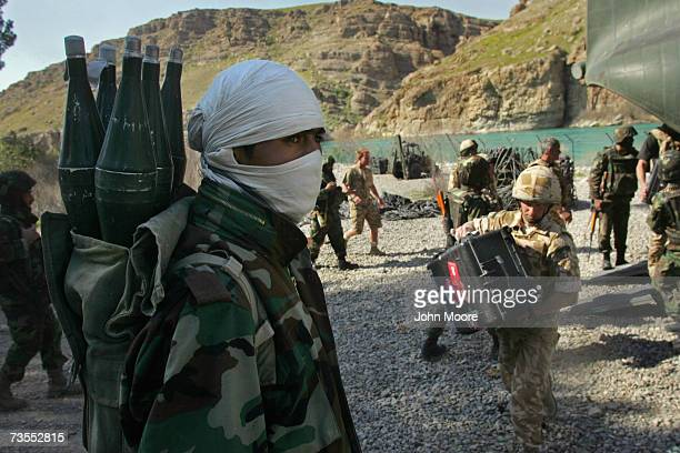 An Afghan army soldier stands by as British forces unload supplies from a helicopter after arriving at Kajaki on March 12 2007 in Southern Helmand...