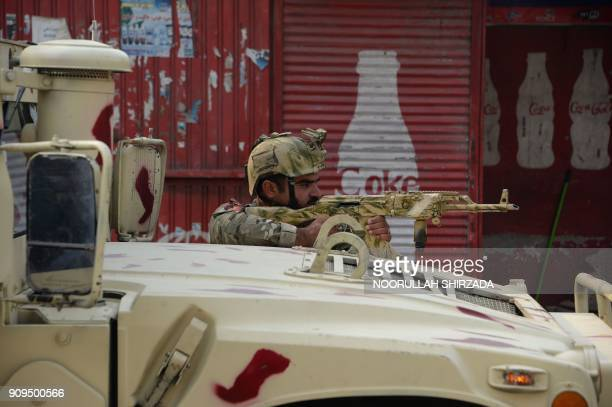An Afghan army soldier takes a position near an office of the British charity Save the Children during an ongoing attack in Jalalabad on January 24...