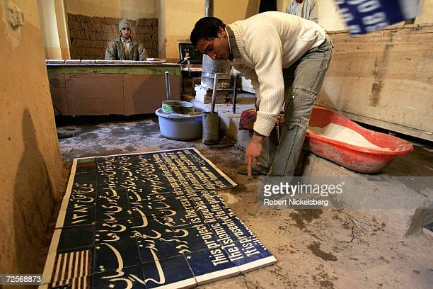 An Afghan artist adjusts clay tiles of a completed plaque inside the 12th century Blue Mosque on February 17 2005 in Herat Afghanistan The...
