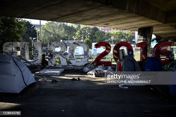 An Afghan asylum seeker sits by large letters refering to the Euro 2016 football championships at a makeshift migrant camp set below the A1 highway...