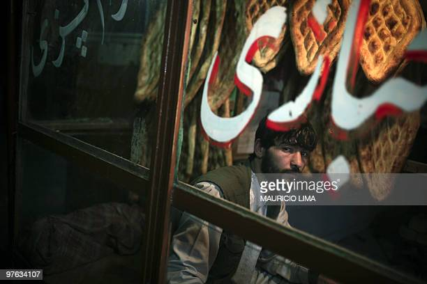 An Afghan baker waits for clients to buy some fresh bread at a bakery in central Kabul on March 10 2010 Iran's outspoken president has accused the...