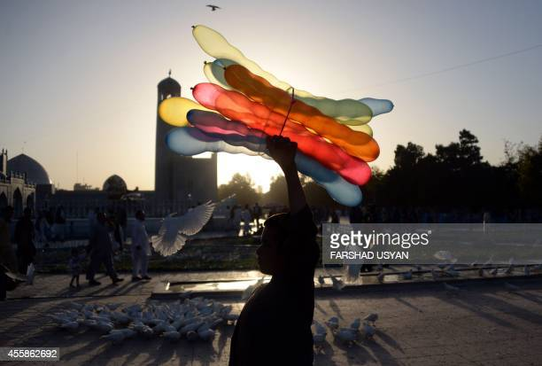 An Afghan balloon vendor walks past the HazrateAli shrine or Blue Mosque in Mazarisharif on September 21 2014 Afghanistan's economy has improved...