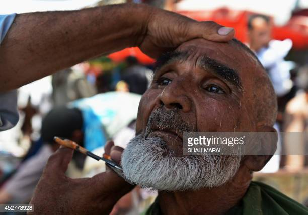 An Afghan barber serves a customer ahead of the Eidal Fitr festival which marks the end of the holy Islamic month of Ramadan at a market in Kabul on...
