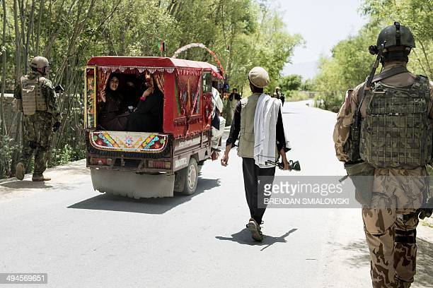 An Afghan bird hunter passes Czech soldiers on patrol near Bagram Airfield in Parwan on May 29 2014 Members of the Czech Army's 4th Rapid Deployment...