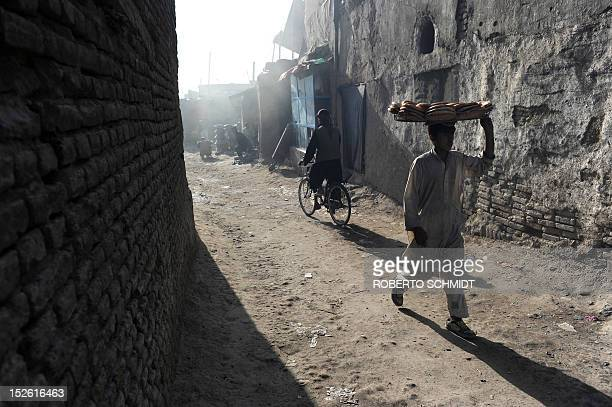 An Afghan boy carries a basket loaded with fresh bread in a back street near a market in Kabul on September 23 2012 There is a growing unease for the...