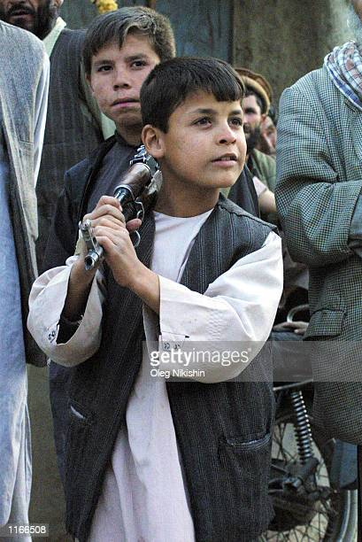 An Afghan boy carries an assult rifle October 4 2001 in the front village of Jabul os Sarache 30 miles north of Kabul Afghanistan