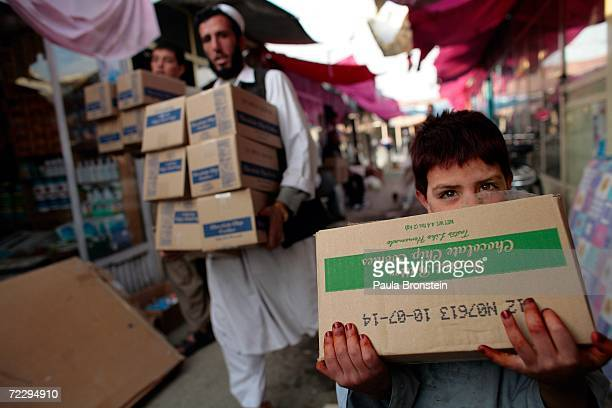 An Afghan boy carries chocolate chip cookies to his father's shop at the Bush Bazaar October 29 2006 in Kabul Afghanistan The small black market...